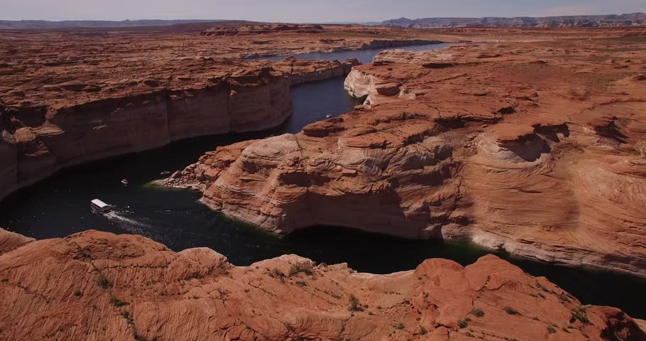 Beautiful views of horseshoe bend and lake powell with red stone canyons, boats and kayakers