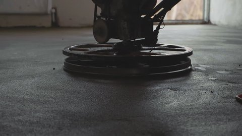 Builder polishing mortar floor at construction site of new appartments. Mechanized grout screed concrete floor close-up slow motion