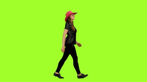 Side view young woman in black leather jacket walks on green background, Chroma key, 4k footage