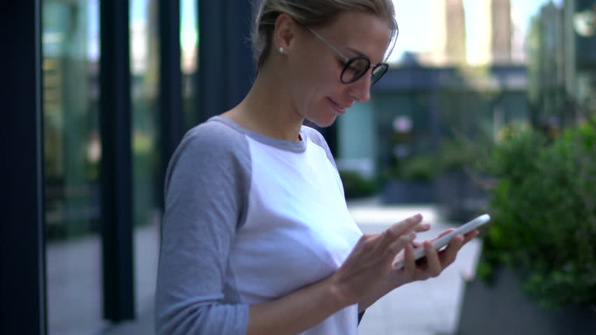 Positive young woman in stylish eyeglasses browsing internet websites on telephone.Blonde student in spectacles chatting online on mobile phone standing on street in windy weather | Shutterstock HD Video #33980479