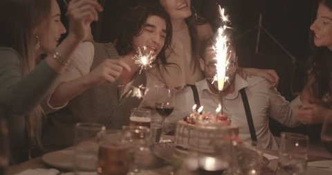 Multi-ethnic friends singing and celebrating man's birthday with sparklers and birthday cake at dinner party