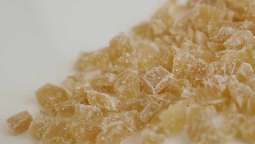 Slow pan on crystallized Zingiber officinale cubes 4K 2160p 30fps UltraHD footage - Cooked and candied ginger root on the table close-up 3840X2160 UHD panning video