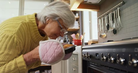 Happy old Caucasian lady wearing oven gloves taking out freshly baked muffins from oven 4K 4k