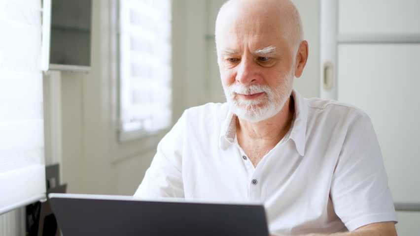 Handsome elderly senior man working on laptop computer at home. Remote freelance work on retirement, active modern lifestyle of older people | Shutterstock HD Video #34008184