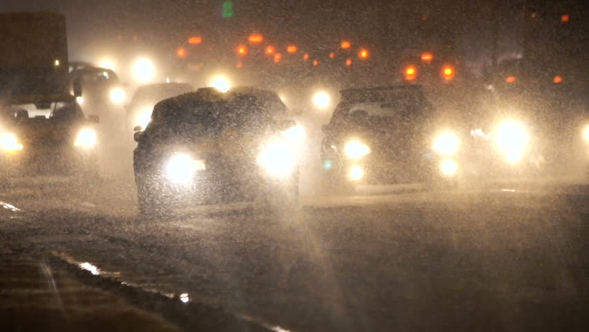 Cars moving in winter storm. Heavy snow and traffic at night.