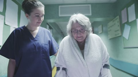 An attractive female medical assistant or nurse helps an elderly lady on crutches to take a walk down a busy hospital corridor.