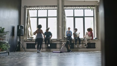 Wide shot of multiethnic group of women sitting on windowsills and chatting before fitness class
