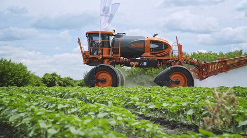 Agriculture fertilizer pesticide spraying. Agricultural sprayer watering plant on farming field. Farming agriculture machinery. Fertilizing plants
