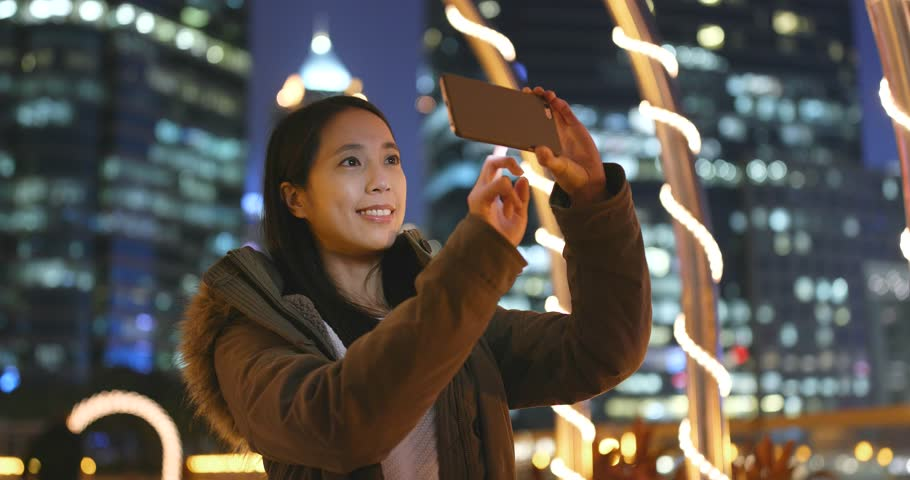 Woman taking photo on smart at night with city background