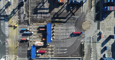 Aerial cinematic 4k zoom in movement , Large container trucks entering with goods through the main entrance gate in the harbor