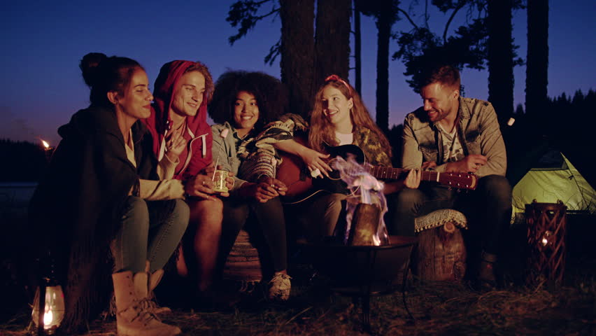 Group Of Happy Friends Playing Guitar Around Burning Bonfire In The Woods Clapping Drinking Laughing And Joking Close Friendship Tourism Travel Party Concept Slow Motion Shot On Red Epic W 8k #34065064