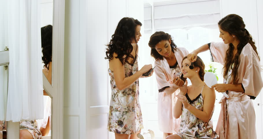 Happy bridesmaids are getting bride ready for wedding at home 4K