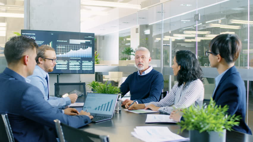 Senior Executive Explains Company's Vision and Potential to His Employees. They are Sitting at Big Table in Meeting Room. TV Screen on the Wall Shows Corporate Growth. Shot on RED EPIC-W 8K Camera.
