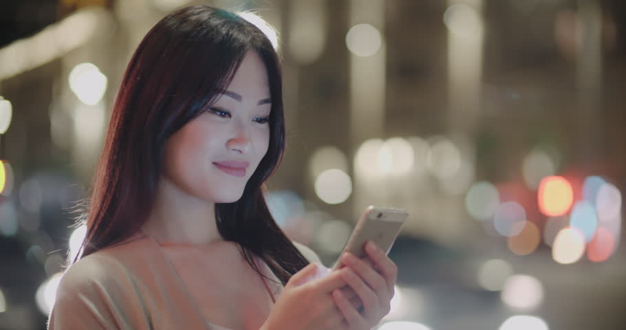 Beautiful Asian girl in the night metropolis, uses a smartphone for communication, writes the message with a smile, Steadicam shot | Shutterstock HD Video #34086634