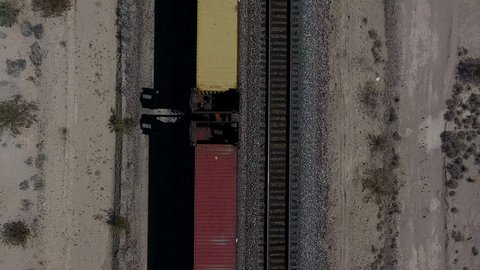 Aerial view of colourful locomotive crossing desert lands on railway near famous interstate asphalt Route 66, bird's eye view of train moving through sandy wild lands transporting delivery