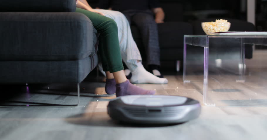 Family eating popcorn during movie night. Three persons, mother, daughter and kid watch television on sofa. They lift feet up when a round robot vacuum cleaner passes to clean the dirty floor.