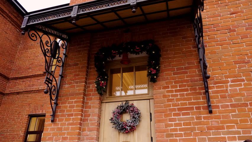 Christmas Wreath Hanging On A Beige Wooden Front Door 4K