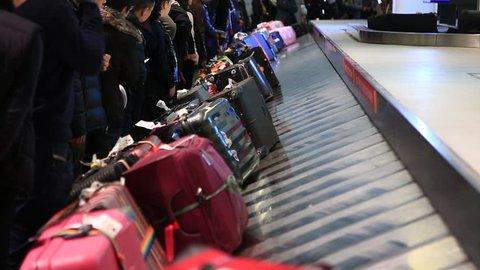 Toronto, Ontario, Canada, December 20, 2017: People pick up luggage at Toronto Pearson Airport.