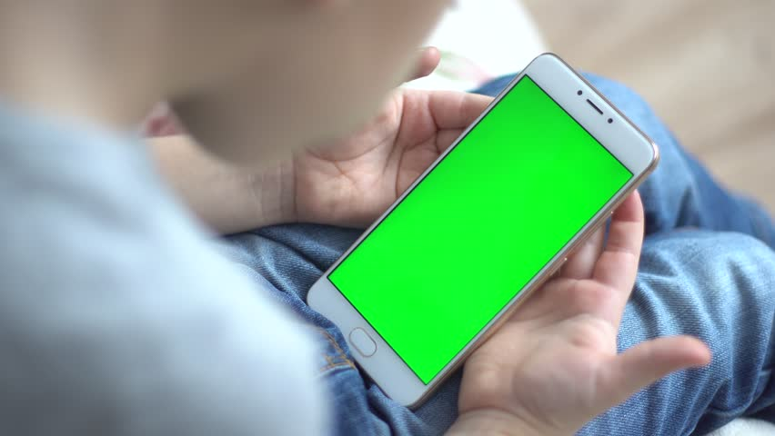 Boy holding mobile phone on green grass lawn with copy space for text. Back view. Technology people connection concept Chroma key mockup | Shutterstock HD Video #34135324