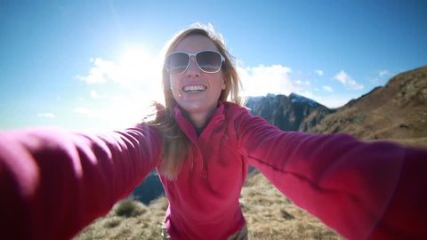 Young woman taking a selfie from mountain top. Hiker tasing selfies at the top of the mountain