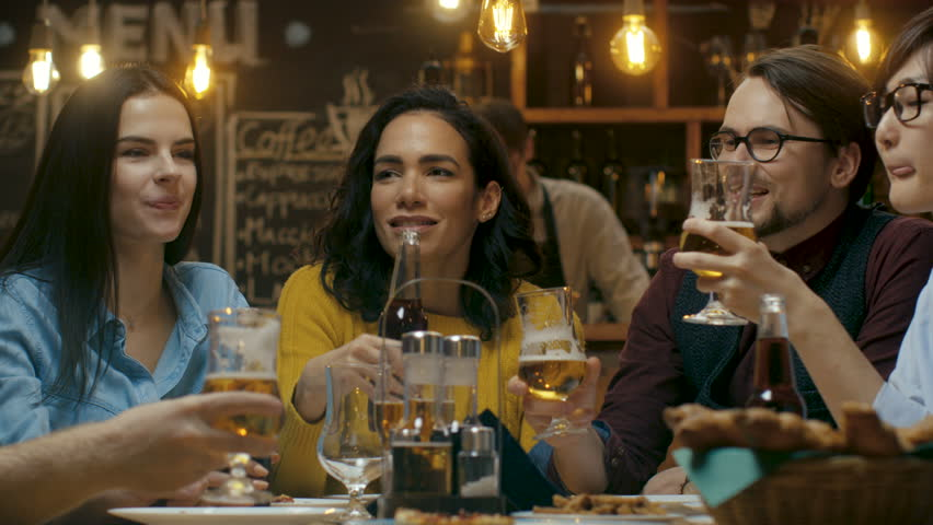 Diverse Group of Friends Celebrate with a Toast and Clink Raised Glasses with Various Drinks in Celebration. Beautiful Young People Have Fun in the Stylish Bar/ Restaurant.  #34161244
