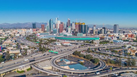 Urban aerial timelapse of downtown Los Angeles convention center, freeways, highways, interstates with heavy traffic on a sunny blue sky day.