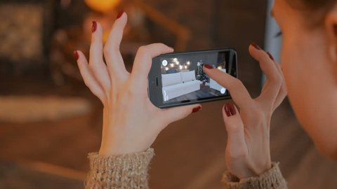 MOSCOW, RUSSIA - DECEMBER 10, 2017. Woman using smartphone with augmented reality app and placing virtual furniture in room. Future and technology concept. Christmas holiday bokeh background