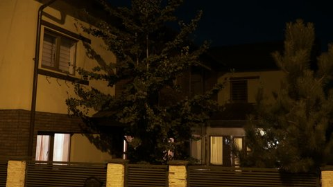 Smart house with pine trees from residential neighborhood turning on lights when the owner comes home inside at night