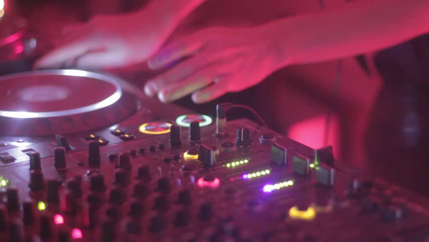 Female Dj is performing her set, tweaking track controls in the night club