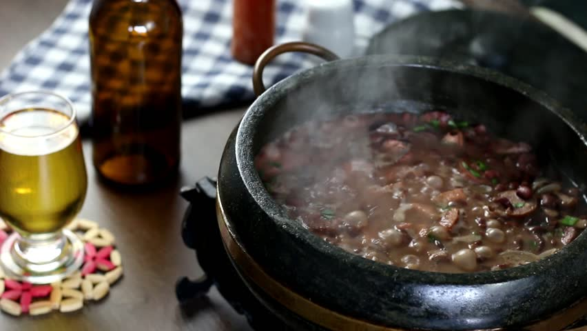 Delicious feijoada served in a stone pot typical of Minas Gerais on a rustic wooden table accompanied by seasonings. Traditional Brazilian food.