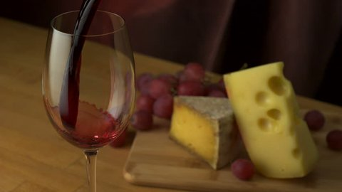 Pouring red wine into glass with grape and cheese shooting with high speed camera, phantom flex.
