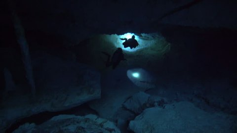 top view on silhouette divers with flashlight in dark ,cenote cave dos ojos