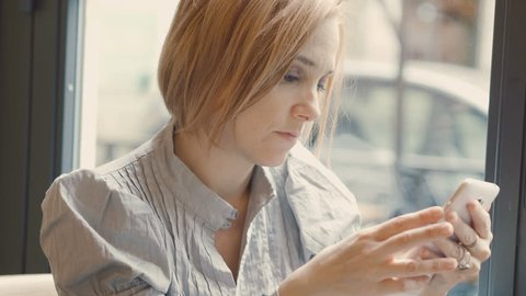 worried and restless woman writing a text message with a smartphone: bad news