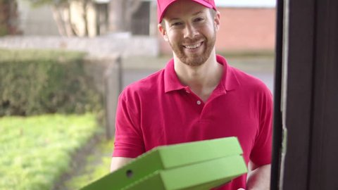Happy Pizza Delivery Man Visits Home With Boxes To A Customer. Fast Food Convenience Delivery And Transportation. A Variety Of Camera Angles Available.