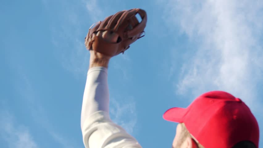 Baseball Catch Success By Fielder Wearing Glove, High Ball From Sky Slow Motion. American Sport And Exercise Outside With Blue Sky. Young Man White Caucasian.
