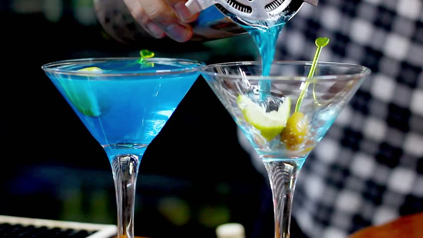 Barman serving blue cocktail drinks into glasses with lemon and olives. Night club, party concept
