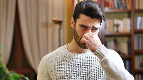 Portrait of caucasian young man closing nose with his hand because of bad smell. Looking at camera. At home, indoor