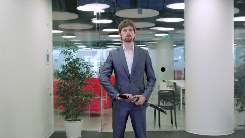 Young businessman practicing with a katana in a modern office room