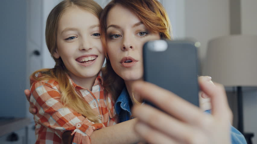 Close up of the smiling mother hugging young daughter and making funny selfies on the smartphone while grimacing. Portrait. Inside