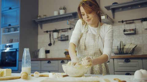 Portrat shot of the attractive woman in the apron kneading a dough for cookies on the table in the kitchen. Inside