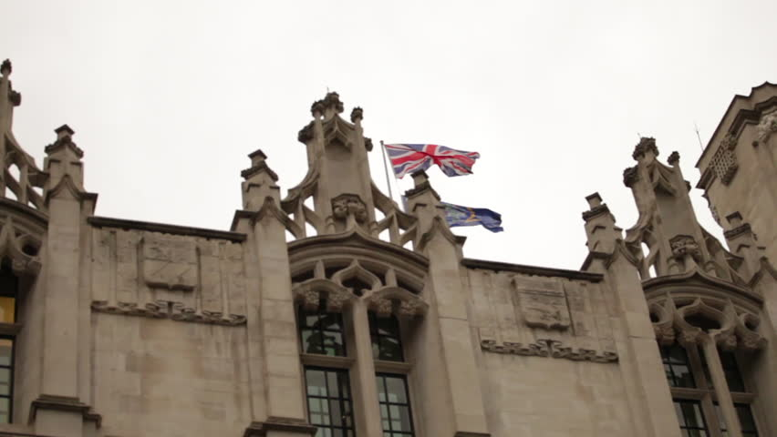 Union Jack flying above an ornate rooftop near Westminster Palace.