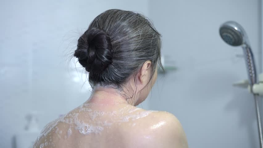Close up view of woman showering in shower room