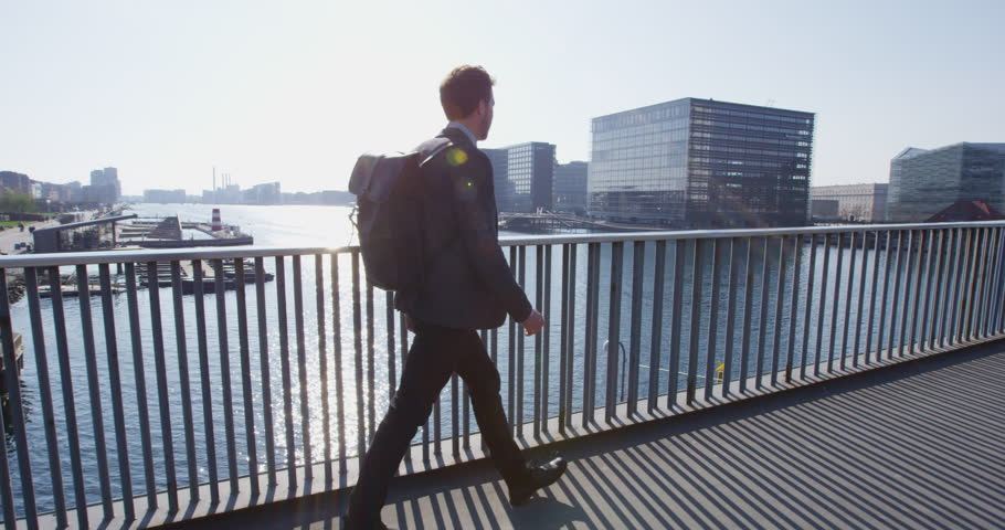 Young urban professional business man walking to work wearing backpack wearing backpack. Businessman in 30s in Copenhagen, Denmark, Scandinavia.