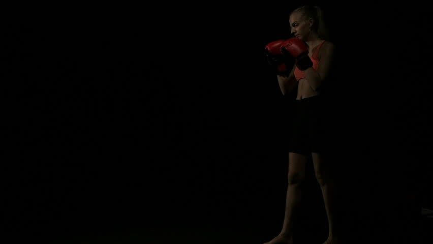 Young intense woman throwing muay thai knee. muay thai style kneeing move. White young beautiful woman. Shot in slow motion. Film look filter.