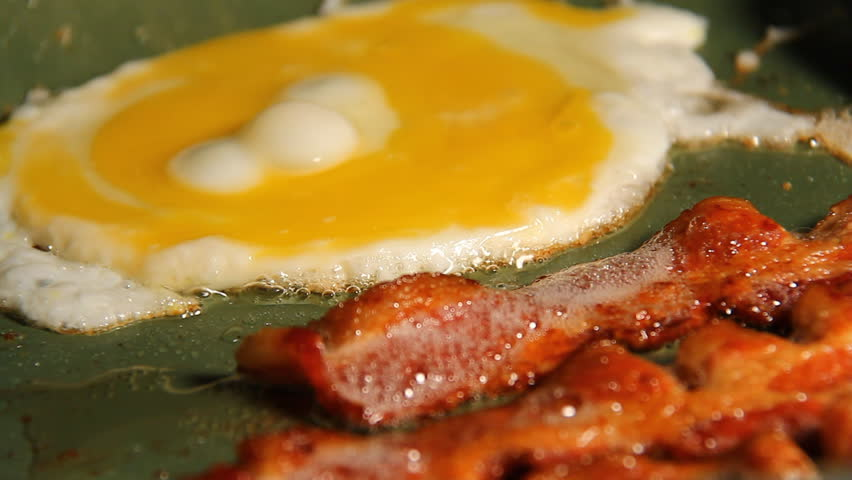 Bacon and Eggs. Three strips of bacon frying in a pan with an egg getting flipped.