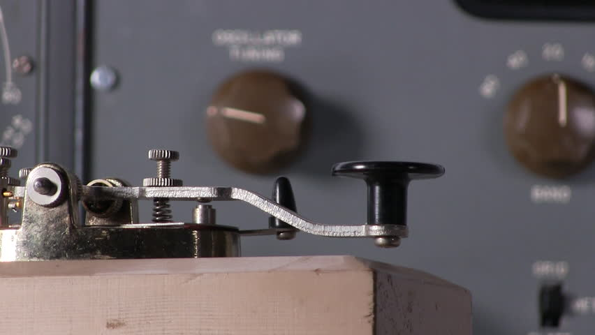 Extreme close-up of finger pressing telegraph key to send morse code radio transmission with vintage electronic hardware engineering military lab test equipment device in the background