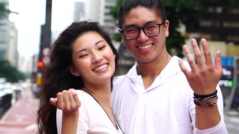 Young Asian Couple Inviting Someone to Come