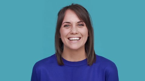 Portrait of cheery female 30s bursting with laughter being in positive after listening to jokes over blue background in studio. Concept of emotions