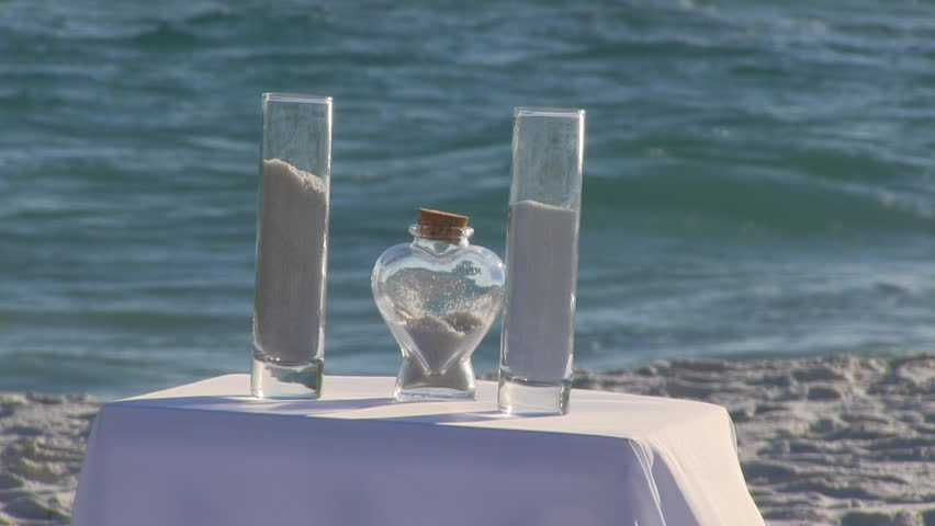 Two glass containers and a heart shaped jar for a wedding sand ceremony sit on a white tablecloth covered table on the beach with the waves breaking in the background.
