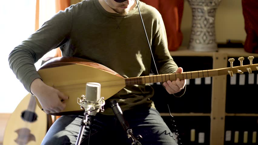 Very slow slide of young man wearing headphones playing baglama saz with microphones in front of instrument and oud and darbuka drums in background in a room with a lot of light and camera slide to th